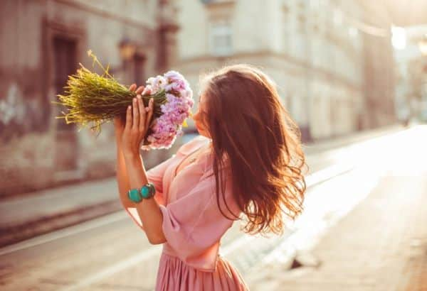 kobieta wącha kwiaty